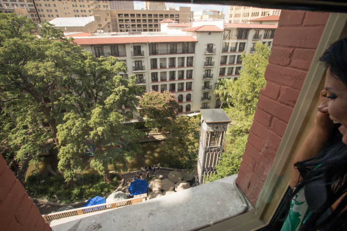 Mary-Margaret Hasslocher looks down onto the River Walk from her window.
