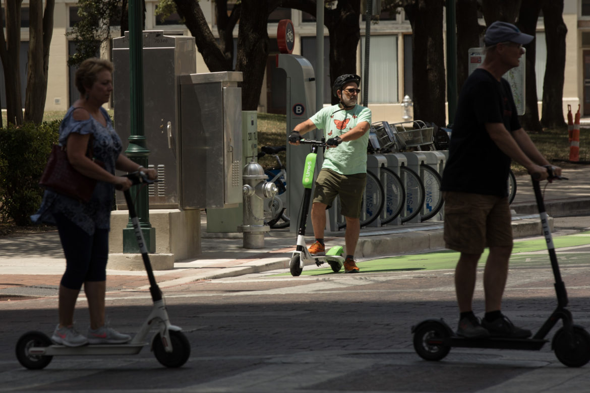 Rivard Report Director Robert Rivard stops at a traffic light while riding a Lime-S electric scooter down Main Street.