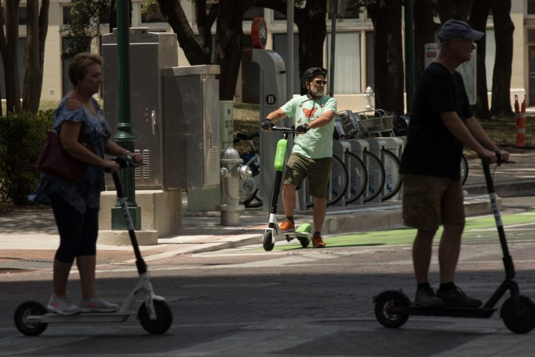 Rivard Report Editor & Publisher Robert Rivard stops at a traffic light while riding a Lime-S electric scooter down Main Street.