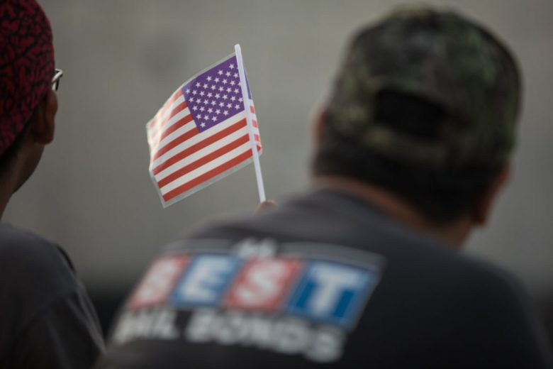 A young man holds an American Flag before the light show.