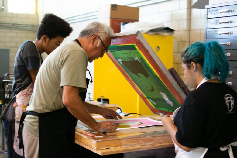 Harvey Mireles, La Printería founder and director, (center) and apprentice Olivia Valenzuela (right) help a student align a print.