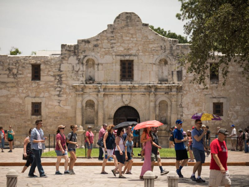 Alamo visitors walk by the mission on the fourth of July.