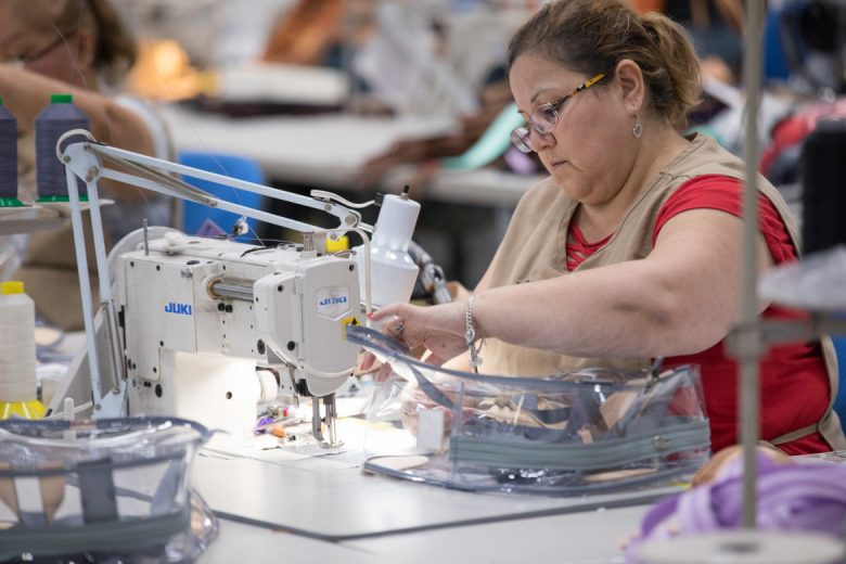 A seamstress works to sew together the clear plastic backpacks.