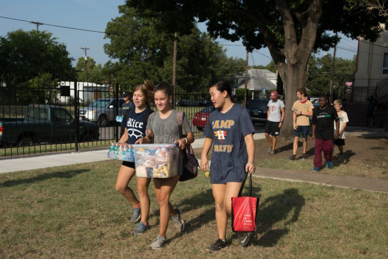 Blueprint Ministries volunteers pack carry packages of food and drinks to the worksite vans.