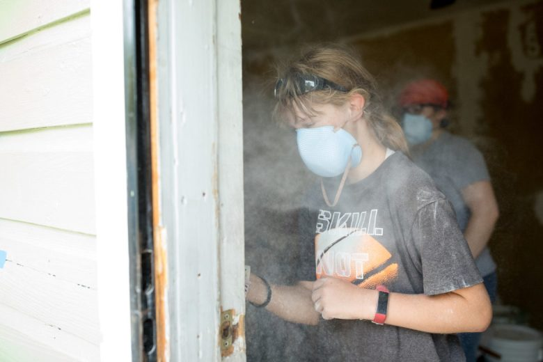 BluePrint Ministries volunteers fill the air with dust as they sand interior walls.
