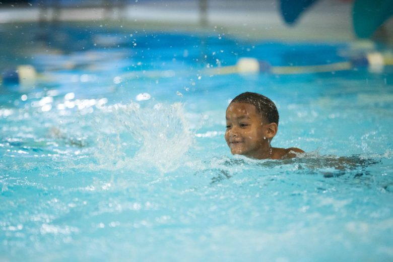 A child smiles as he swims across the pool under lifeguard supervision.