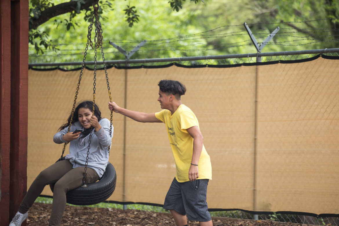 Inner City Development participants play at a playground in the backyard.