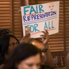 Signs demanding fair representation are held up in the audience of Commissioners Court.