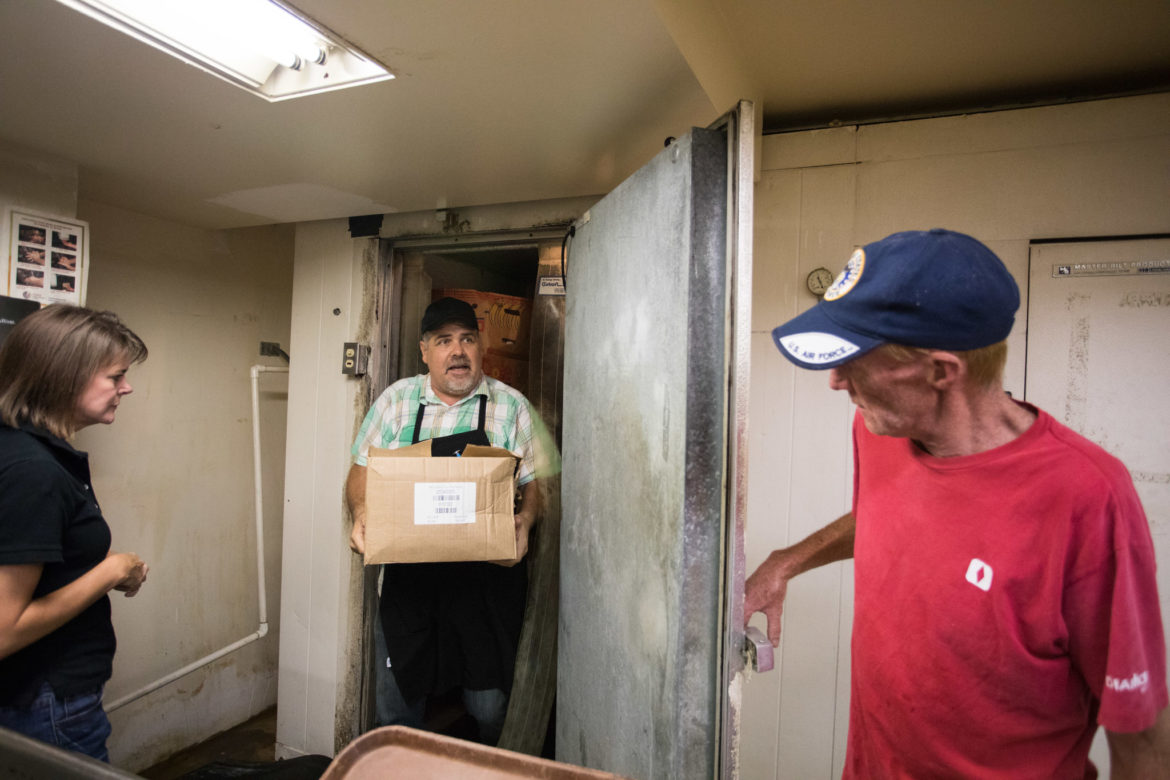 (From left) Lori Chidgey, Corazon Ministries executive director; John Chadwell, Corazon Ministries kitchen manager; and Gerald Wilding, Corazon Ministries volunteer, chat while Chadwell brings cheesecake out of the freezer.