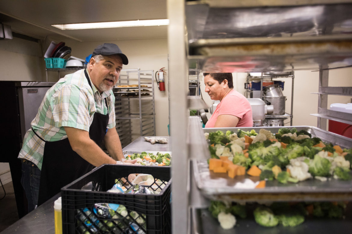 John Chadwell, Corazon Ministries kitchen manager, (left) teaches Maria Rincon, Corazon Ministries volunteer, how to prepare the vegetables.