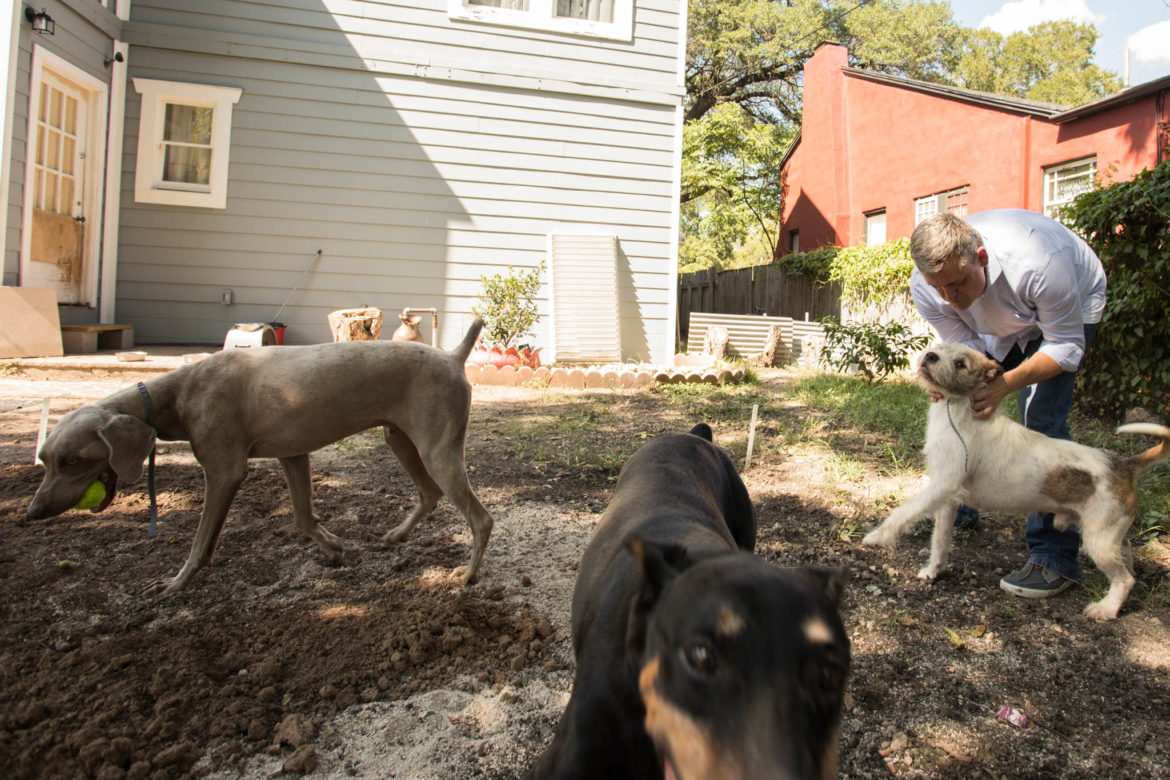 Justin Holley plays with three of his dogs in his backyard.