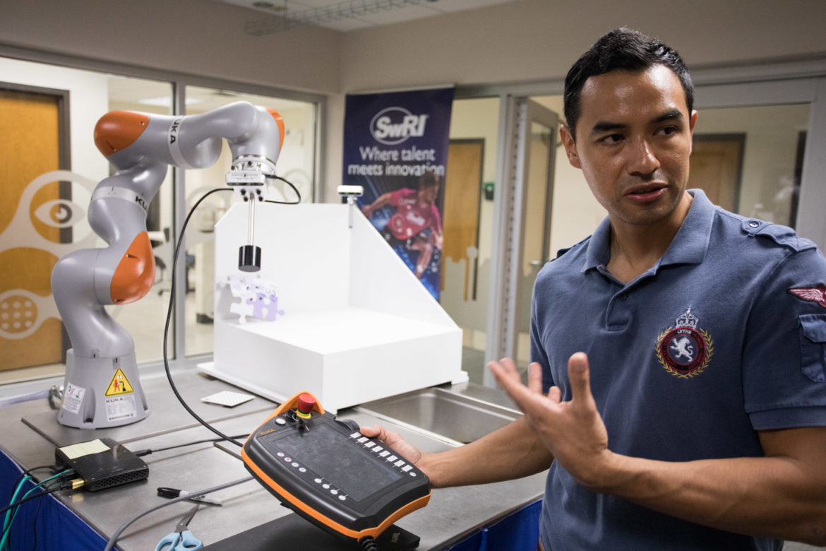 Jorge Nicho, mechanical engineer, programs a KUKA iiwa robot in the Collaborative Robotics Laboratory at Southwest Research Institute.