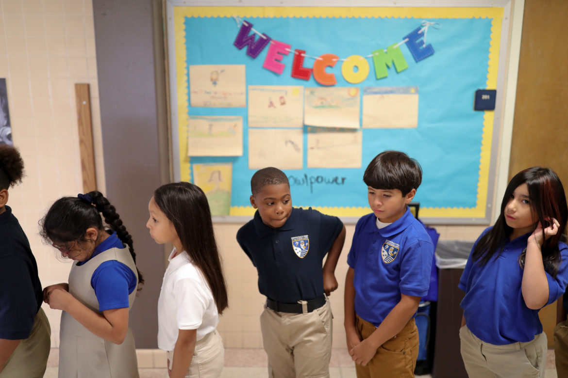 Students stand in line in the hallways of Democracy Prep at Stewart Elementary.