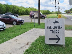 Signs for helicopter tours, gates, and barbecue line Mission Road at Stinson Airport's main entrance.