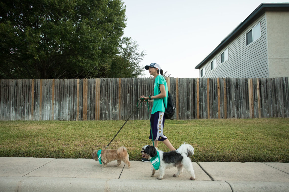 """Brittany """"Brimo"""" Morales walks the dogs through their neighborhood."""