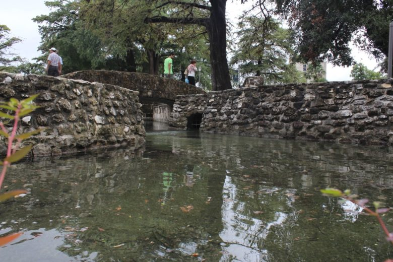 Visitors to San Pedro Springs Park cross a bridge over the headwaters of San Pedro Creek. The springs began flowing again after recent rains replenished the Edwards Aquifer.