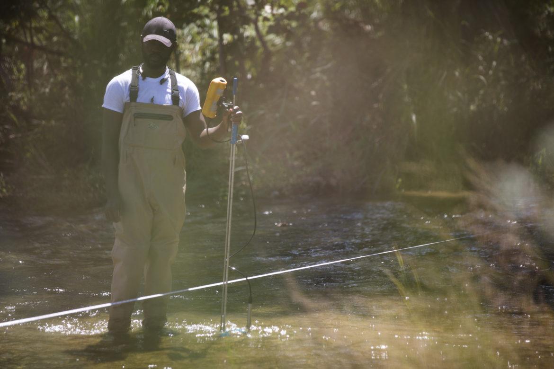 UTSA graduate student Adeyeye Adebayo measures the water at different points along Cibolo Creek.