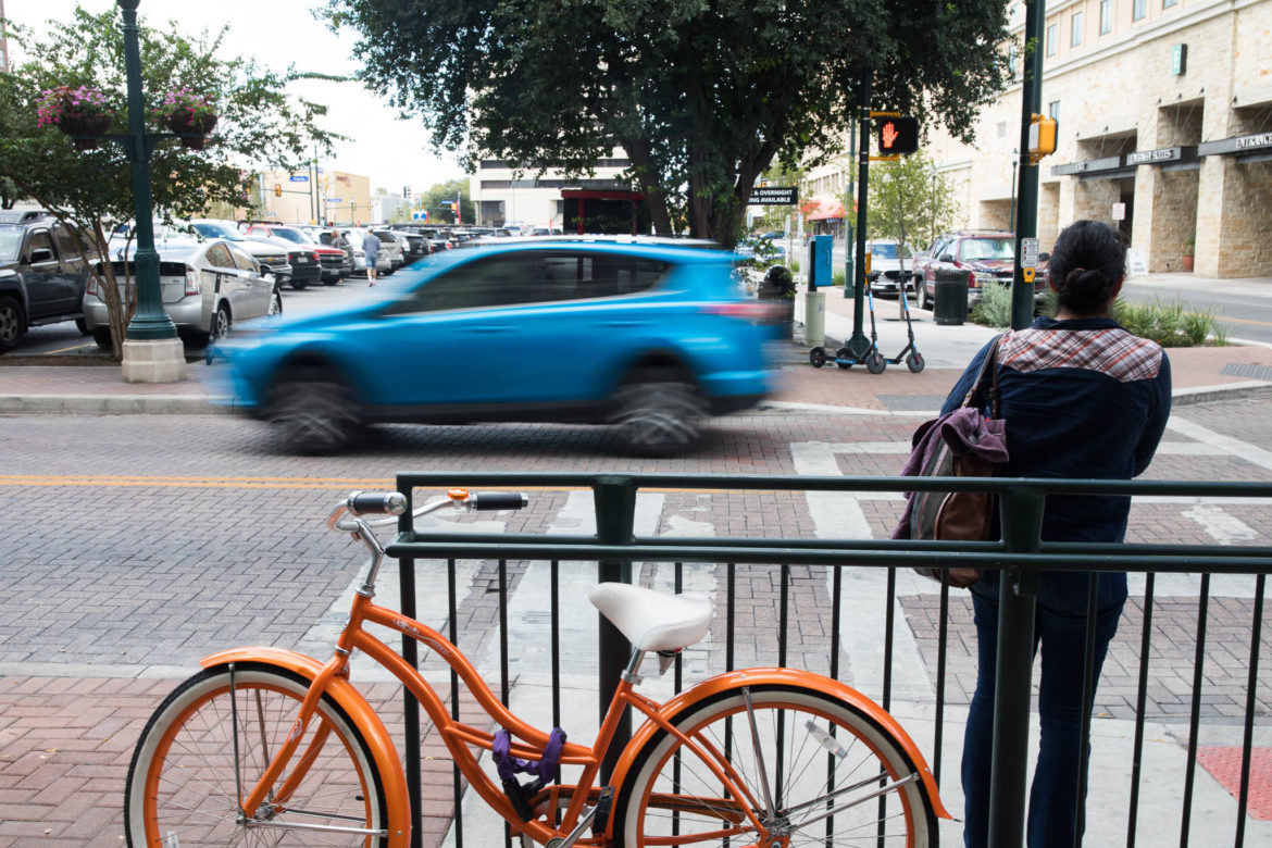 Cars, bikes, scooters, and people all occupy the streets of downtown San Antonio.