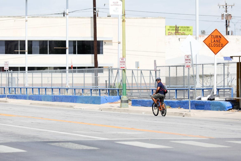 A cyclist heading North on Broadway near Brooklyn Avenue checks backward for vehicles.