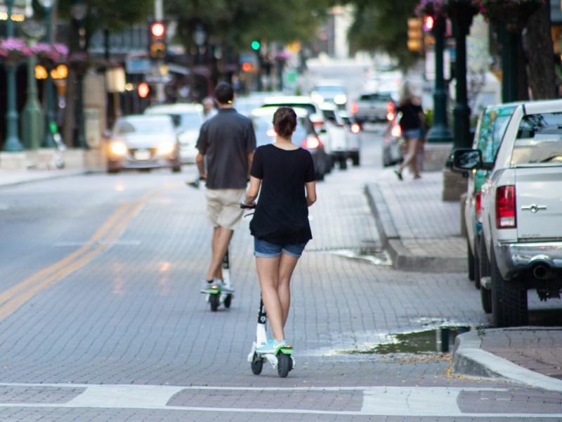 People on scooters turn onto East Houston Street.