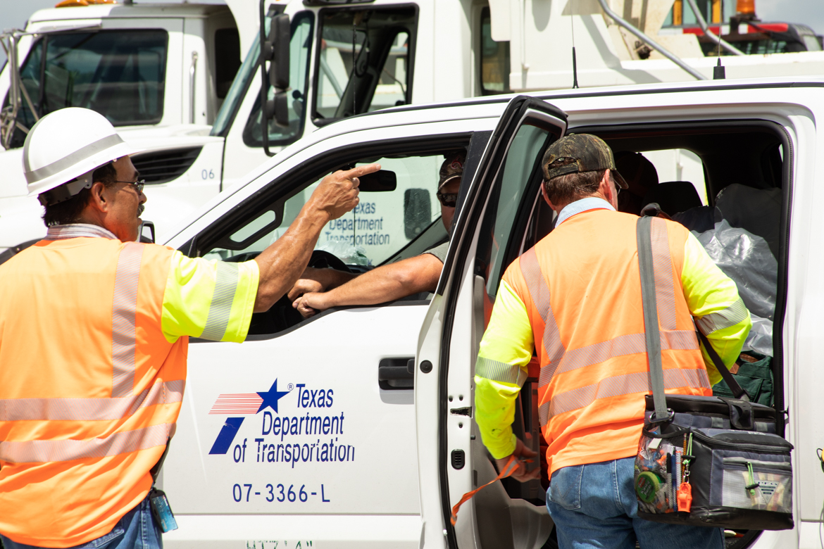 TxDOT employees direct vehicles carrying emergency equipment in preparation of response to costal floods.