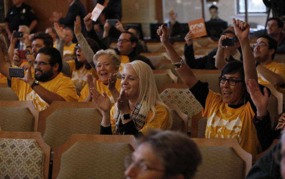 Alamo employees Christina Robertson (center left), Jessica Gonzales, and others cheer after City Council approves the Alamo Redevelopment Plan.