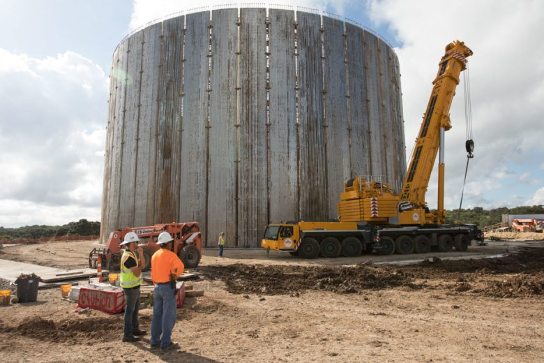 DN Tanks employees stand in front of a 10-million gallon water storage tank, part of the San Antonio Water System's Agua Vista site. The site will be the end point of the Vista Ridge pipeline.