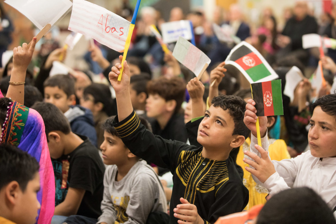Students representing Afghanistan wave flags in the air.