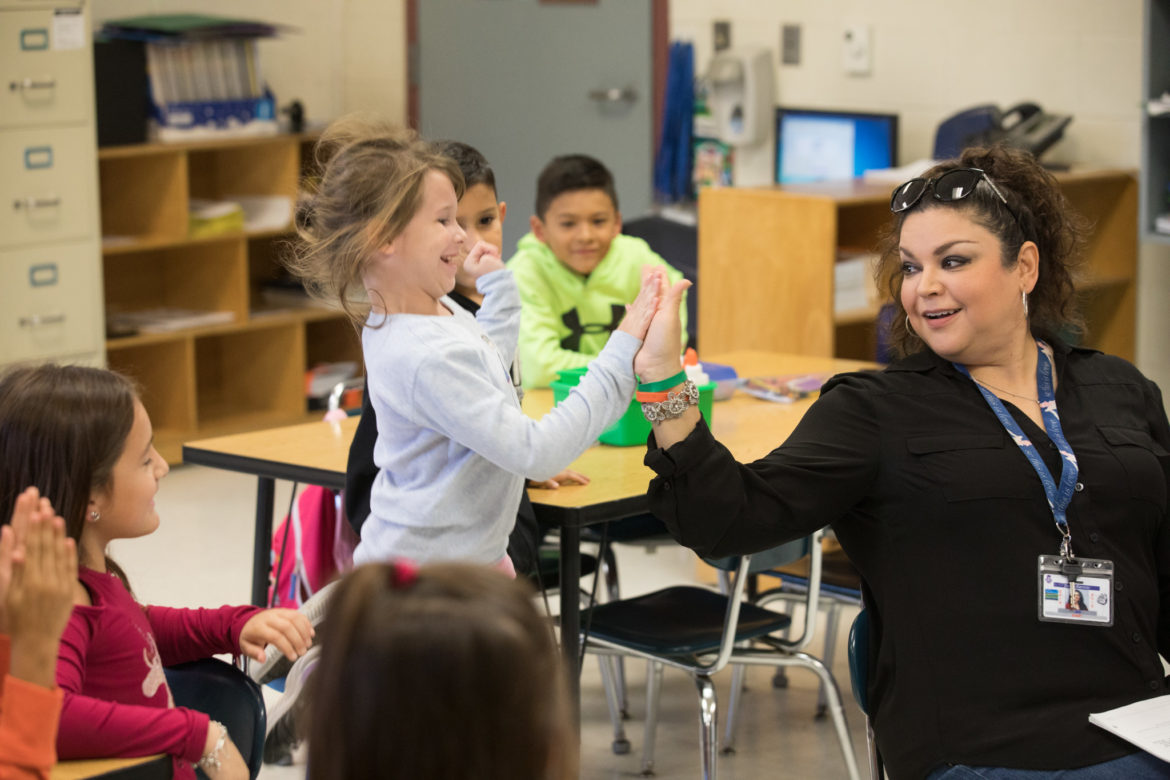 First grader Brooke Dresch (left) high-fives Evelyn Ramirez, Somerset Elementary School first grade teacher, after getting the right answer to a question during the Yes! Our Kids Can program.