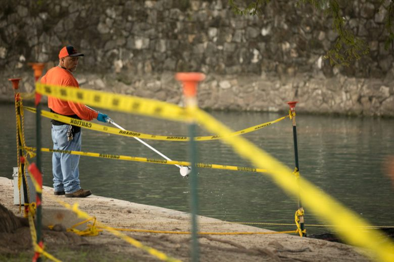 City workers use tools to clean up debris floating in the San Antonio River in preparation of the 2017 bond project repairing portions of the river in Brackenridge Park.