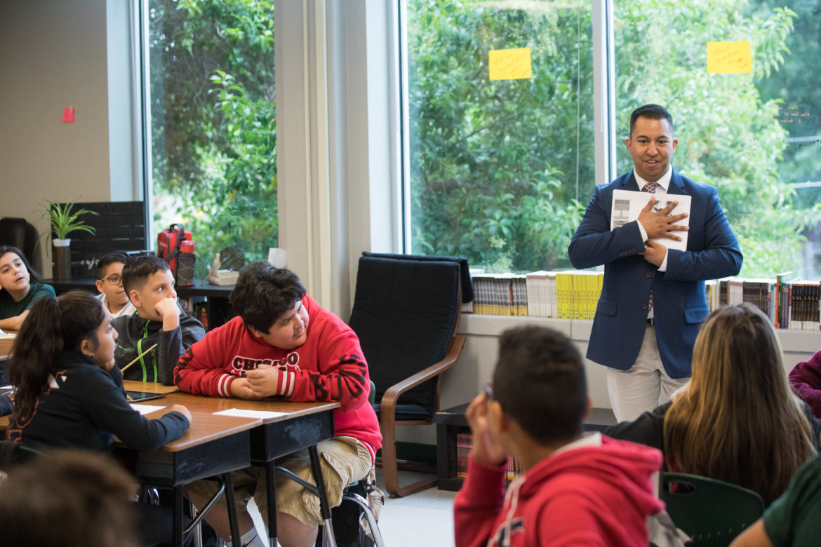 Cotton Academy Elementary School teacher Adam Rodriguez works with his students on a literature assignment.
