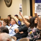 Protesters urging the commissions to reject the proposal hold up signs during the meeting.