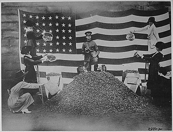 Women of Boston are lending a helping hand in the drive for peach stones, which are being used by the Government in the production of gas masks. This Tableau was arranged to help in the campaign.