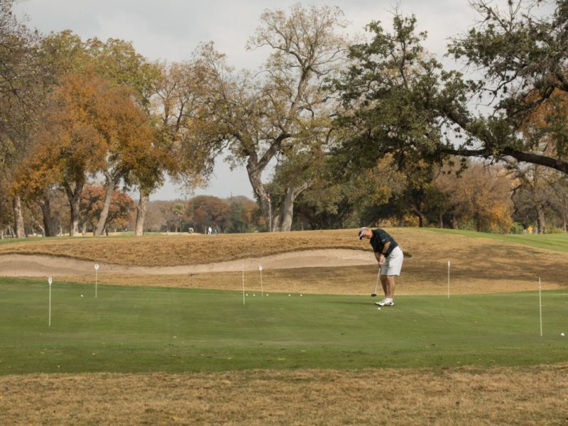 A golfer practices his swing before entering the course at Historic Brackenridge Park Golf Course.