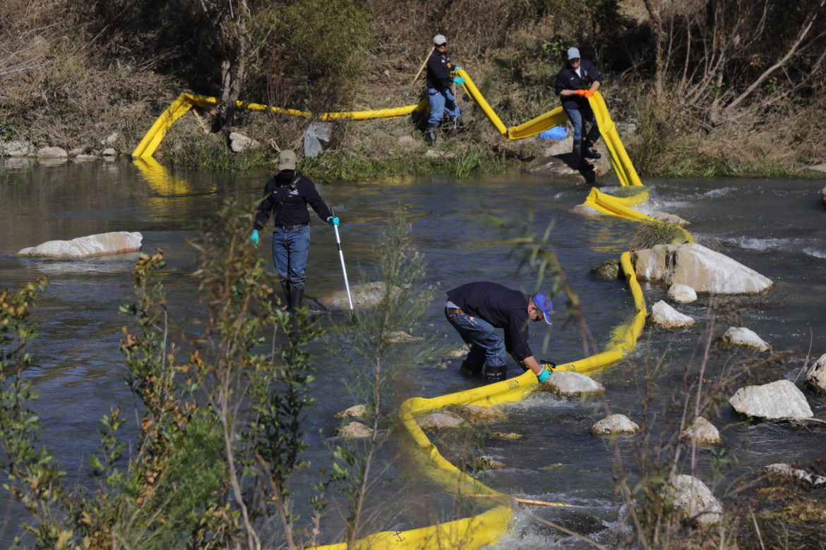 Emergency response personnel with Calumet Specialty Products removing a boom placed across the San Antonio River after a small spill of naphtha on Thursday, Nov. 15, 2018.