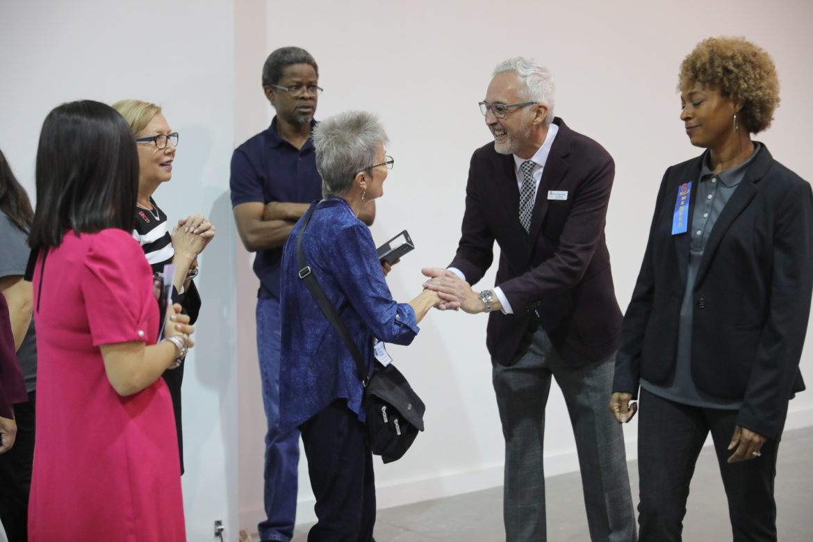 Texas Diaper Bank CEO Jorge Medina shakes hands of supporters and visitors of the newly expanded facility.