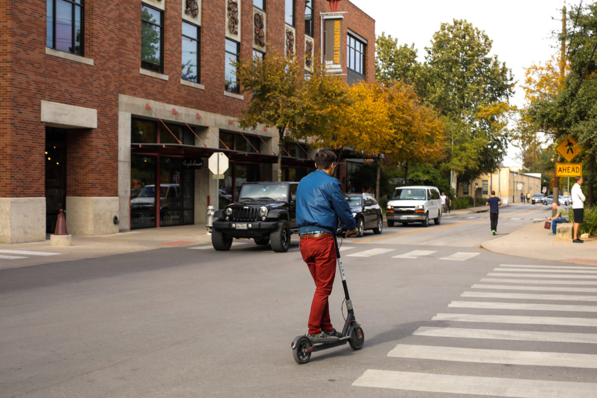 Scooters cross in front of the Pearl as pedestrians and vehicles share the road.
