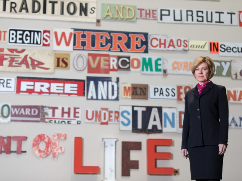City Manager Sheryl Sculley stands for a photo in front of the pubic art piece The Story of Civilization with Discarded Signs by artist Gary Sweeney.