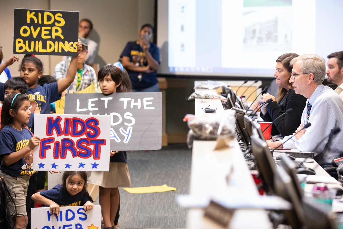 Beacon Hill Academy students hold up signs urging Historic and Design Review Commission members (right) to ease the way toward demolition for a 1915 campus building.