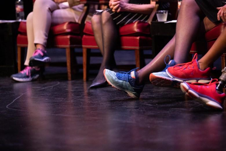 The women on stage wear sneakers.
