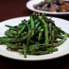 """(From left) dry-wok sautéed green beans and fish fragrant """"spicy garlic"""" eggplant."""