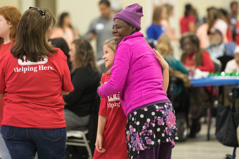 Joni Smith (right) hugs H-E-B volunteer Emma Castelo, 11, after sharing a dance.
