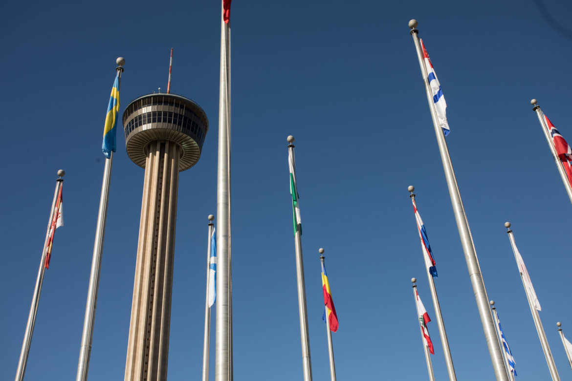 Tower of the Americas in the background of the flags in front of the Institute of Texan Cultures.