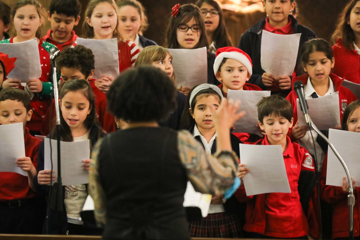 Students sing songs in a choir arrangement in-between the play.