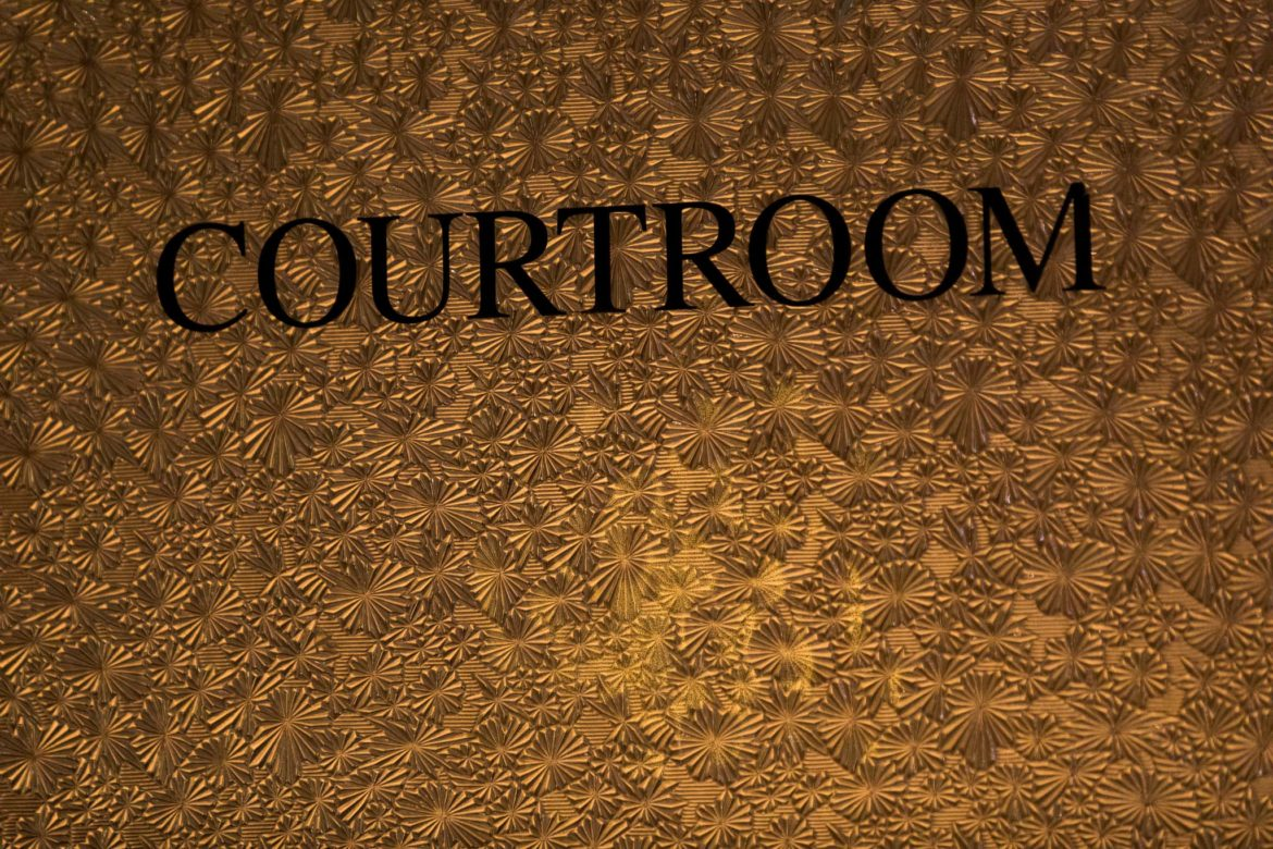 A sign indicates a courtroom inside the Bexar County Courthouse.