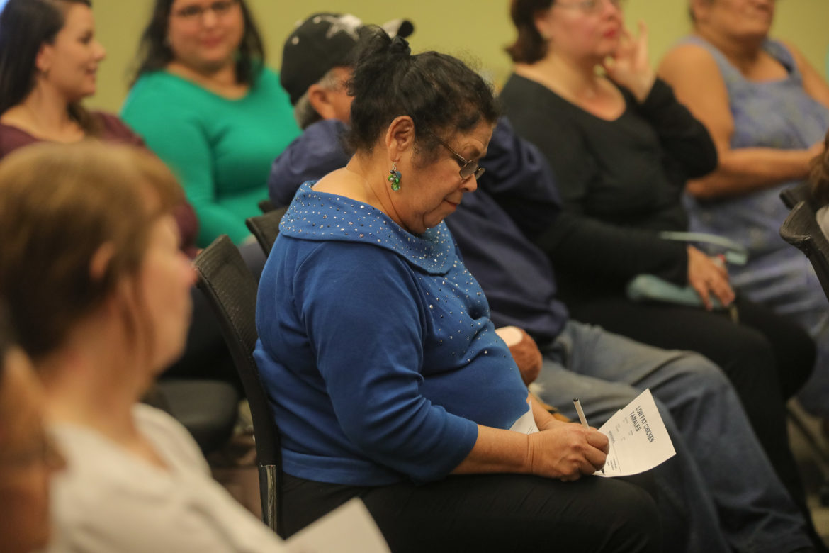 Community members jot down notes on a recipe handed out that details how to cook low-fat chicken tamales.