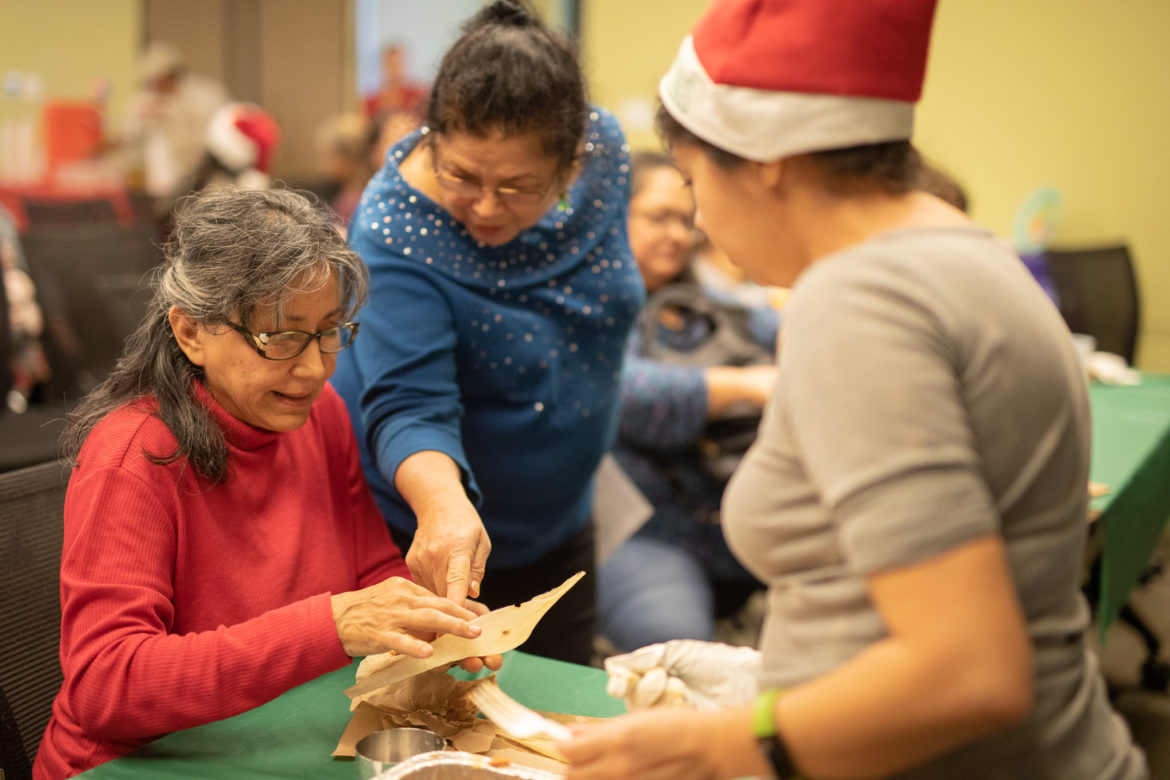 Terry Garcia (left) spreads masa and prepares the tamale to be filled with healthy ingredients.