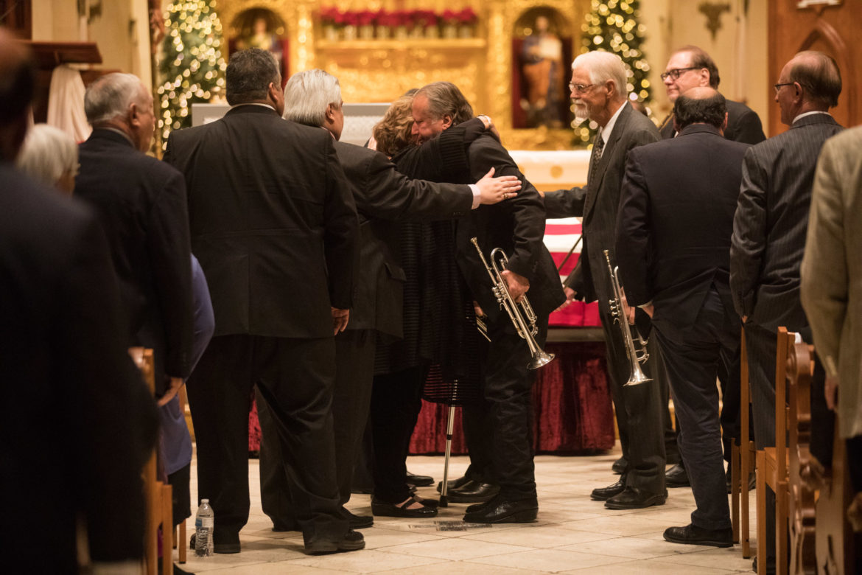 Members of the Paul Elizondo Orchestra hug Irene, the wife of deceased Paul Elizondo.