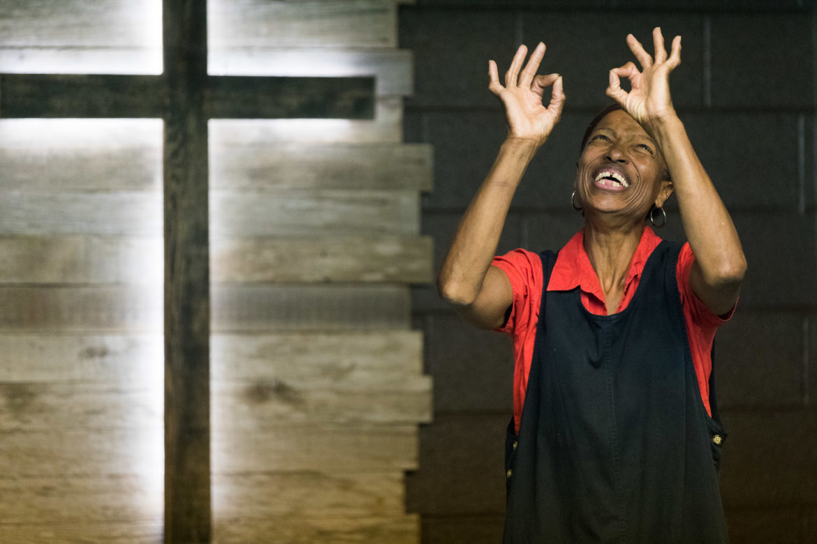 Ophelia Thomas holds her hands up with the signs for 'okay' during a musical performance at the Family Deaf Church.