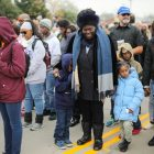 Elizabeth Holmes with (left) Jaleel Pickens (8) and Ava Albert (6) stop and listen to a prayer during the march.